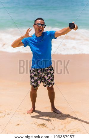 Man In Sunglasses Sits With A Smartphone In The Hands And Making Selfie On The Phone Near The Sea