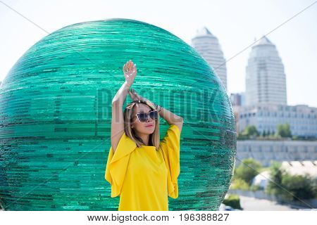 Beautiful Blond Young Woman In A Yellow Dress, Against A Background Of Glass Balls
