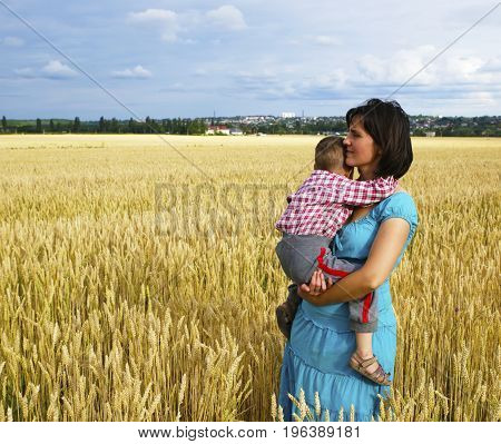 Young mother plays with her son on a wheat field. Photo for microstock