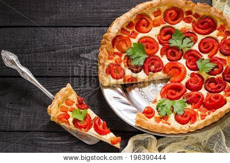 Delicious homemade pie with cheese cottage cheese pepper rolled up in roll in form of flower. Large cake on metal round plate slice on scapula cherry tomatoes parsley on yellow gauze napkin