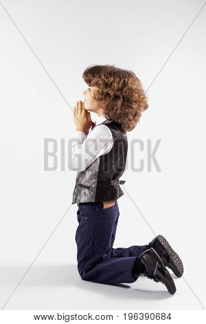 Cute Curly-haired Boy In A Silver Vest Kneels And Prays. Gray Background.