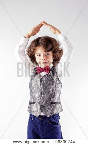 Curly Cute Boy In Waistcoat And Bow Tie Shows Hands Shelter. Close-up. Gray Background.
