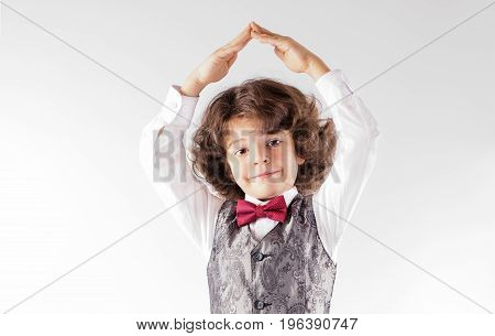 Curly Cute Boy In Waistcoat And Bow Tie, He Folded His Hands Over His Head. Close-up. Gray Backgroun