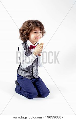 Cute curly-haired boy on his knees hands clasped in prayer and looking forward. Close-up. Gray background.