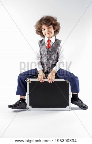 Cute curly little boy sitting on the black suitcase and looking into the camera. Gray background.
