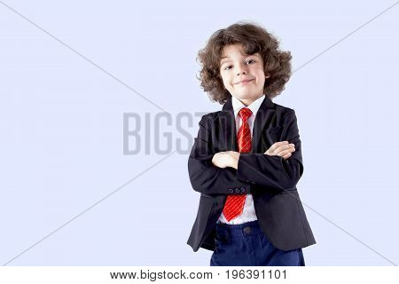 Curly Cute Boy In A Business Suit Stands With His Arms Crossed, Looking At The Camera. Full Length.