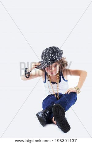 Cute Curly Rapper In A Baseball Cap Sitting On The Floor And Looking Into The Camera. Gray Backgroun