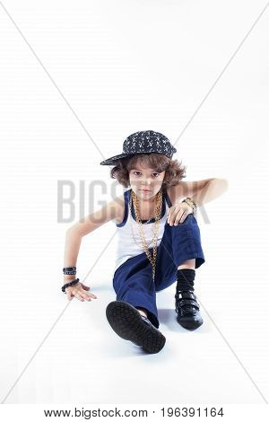 Little Curly Boy In Fashionable Clothes Sitting On The Floor And Looking Into The Camera. White Back