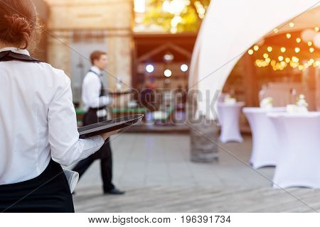 Waiter holding an empty tray in outdoor cafe. Catering service