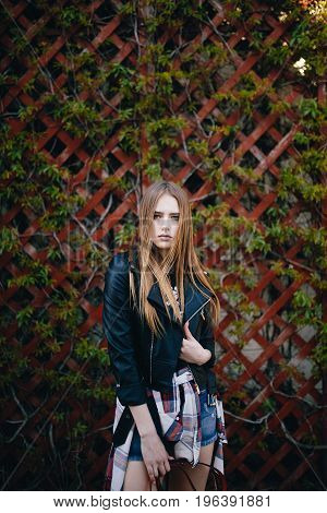 Fashion portrait pretty young woman. Long hair girl in black jacket outdoor