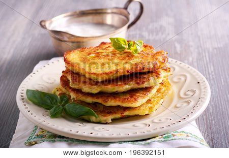 Stack of zucchini and feta fritters on plate