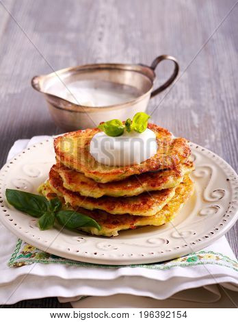 Zucchini and feta fritters with sour cream on plate