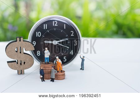 Miniature worker and businessman standing on the stack coin beside by the dollar sign and alarm clock using as a business concept.