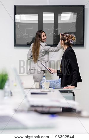 Young female colleagues drawing an algorithm on the screen and smiling in the office. Vertical indoors shot.