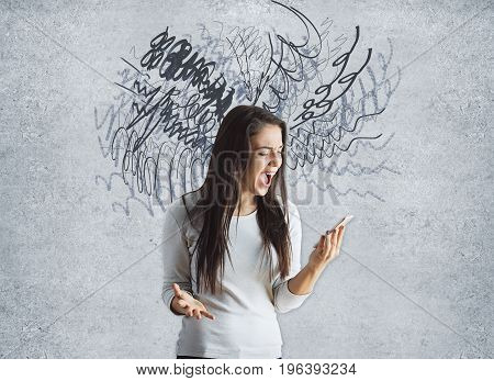 Confused young woman shouting at smartphone on concrete background with scribble. Confusion concept