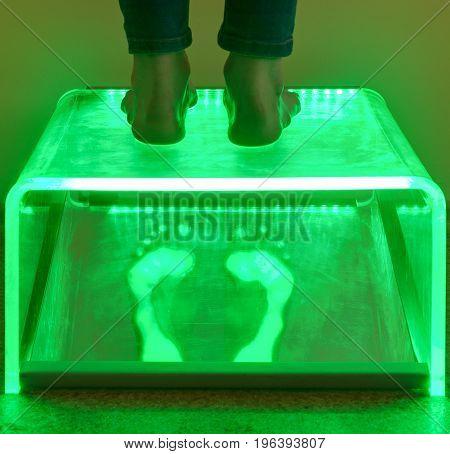 examining feet using Plantoscopy in medical office