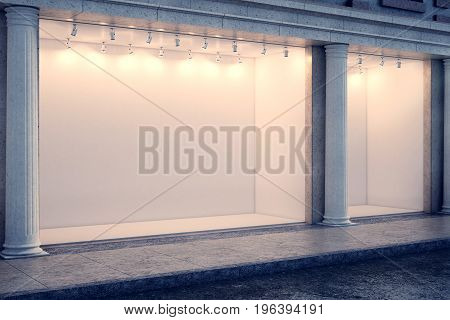 Side view of building with illuminated clear storefront and columns in night city. Advertisement and commerce concept. Mock up 3D Rendering