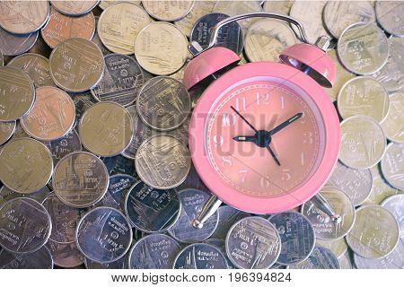 Stack of coins with pink fashioned alarm clock for display planning money financial and business accounting concept time is money concept with clock and coins time to work at make money vintage color tone