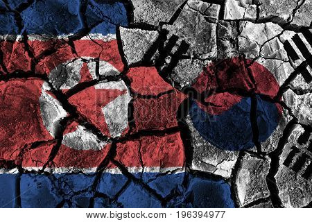 North and south korea flag on cracked ground . Confliction and crisis concept .
