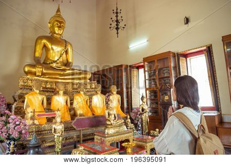 Chinese asian traveler sincere praying at old wat pho temple with golden buddha in front of her. asia travel holiday vacation concept.