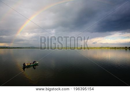 Pollonaruwa Sri Lanka December 20 2015: At dawn Sri Lankan fishermen in a boat on the lake. Above the lake is a rainbow.