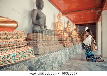 Happy Female Student Kneeling In Front Of Buddha