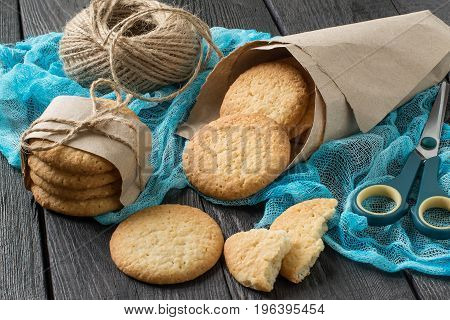 Delicious homemade cookies with onion sesame and spices in paper bag on table with blue gauze napkin as well as a twine for packing