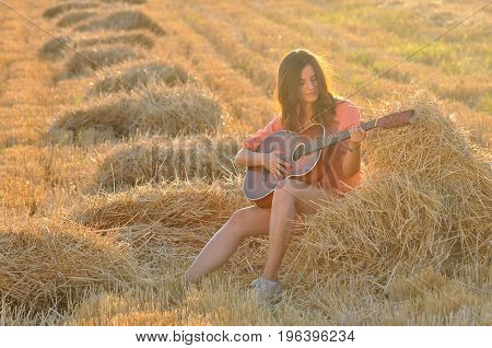 Happy cheerful girl playing guitar at hay bale at sunset. Young woman with guitar in the field