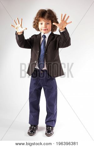 Funny Curly Boy Stands And Shows Ten Fingers. Full Length. Gray Background.