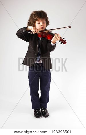 Clever Little Violinist In A Business Suit Playing A Musical Instrument. Gray Background.
