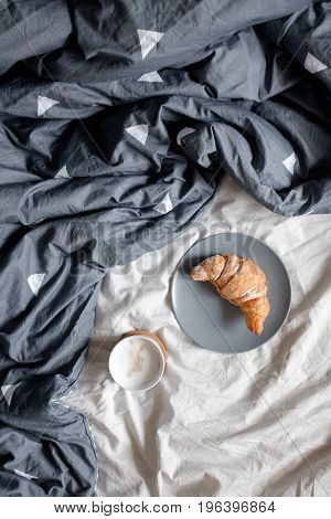 Top view of a cup of coffee and a croissant on a plate on a cozy bed
