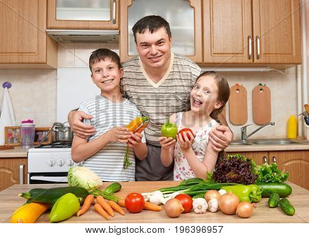 Father and two children, girl and boy, having fun with fruits and vegetables in home kitchen interior. Healthy food concept. Happy family.