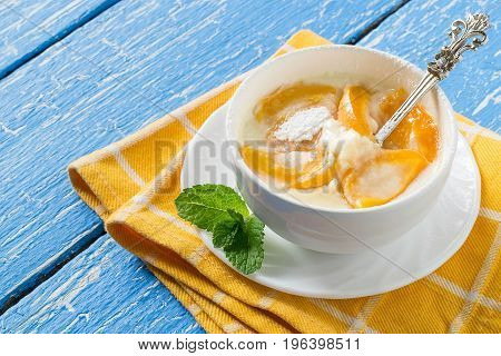 Delicious creamy apricot dessert in white cup on yellow napkin. Summer desserts with fruits. Dietary and healthy food