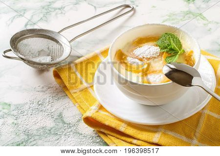 Delicious creamy apricot dessert in white cup on yellow napkin. Sieve with powdered sugar. Summer desserts with fruits. Dietary and healthy food