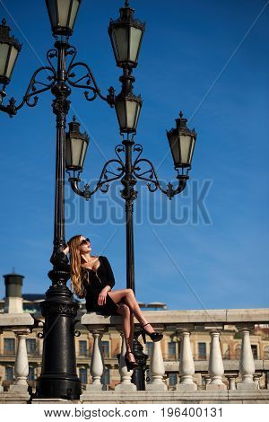 Lady in black dress sitting on baluster railing under vintage street lamp on blue sky background