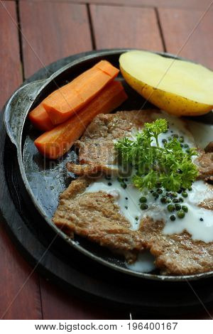 Grilled pork steaks with baked potatoes and vegetables.
