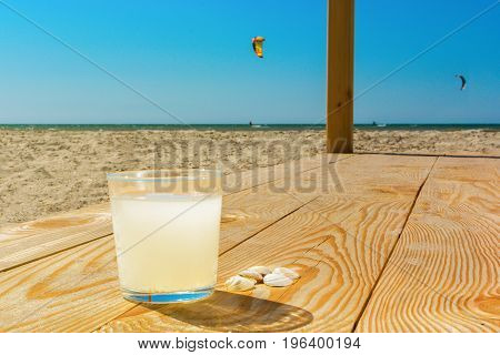 A glass of soda lemon water on the wooden boards on the beach. Kiteboarders in the background.