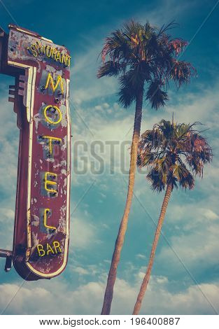 Retro Worn Vintage Neon Motel Sign And Palm Trees