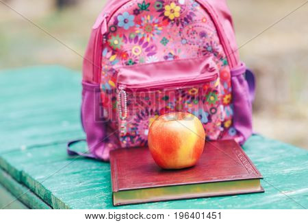 On the bench lie the book backpack and apple