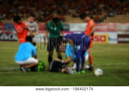 Blurry Doctors And Referee With Injured Player At The Football Match