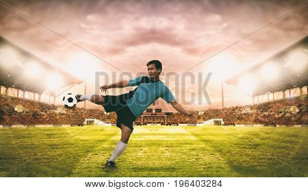 Soccer And Football Player Shooting Football On Goal At The Football Stadium On Night. Blurry And So