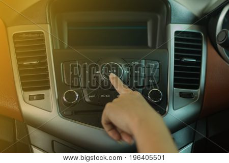 Women press buttom on car radio and happy for travel