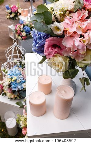Wedding ceremony decorations bouquets of flowers eustoma and roses, candles in restaurant outdoors.