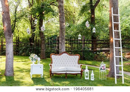 Wedding ceremony decorations bouquets of roses, sofa, staircase in restaurant outdoors.