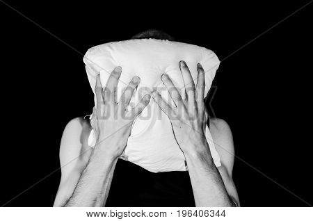 Miserable and depressed man cover his face with pillow and cry. Dark image. Hard contrast. Dark background.