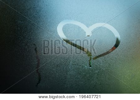 Heart painted on wet glass. Heart sign painted on wet glass.