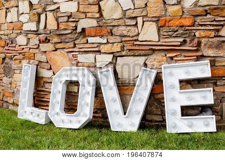 A word of love near the stone wall. Photo area in wedding decoration in the park