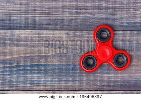 A red hand spinner lies on a wooden table. There is space for text on the left