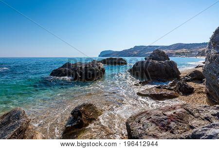 Colourful rocks in crystal clear turquise waters of paliochori beach in Milos island Greece