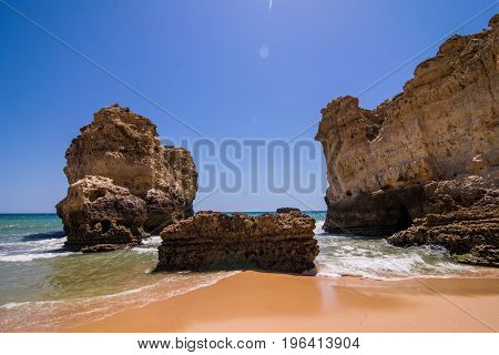 View Of Beautiful Sandy Beach On Ocean Breeze With Cave In Summer Sunny Day